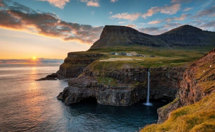 Múlafossur Waterfall with the tiny village Gásadalur in the background. This waterfall is a main reason why tourism in the Faroe Islands is on the rise.